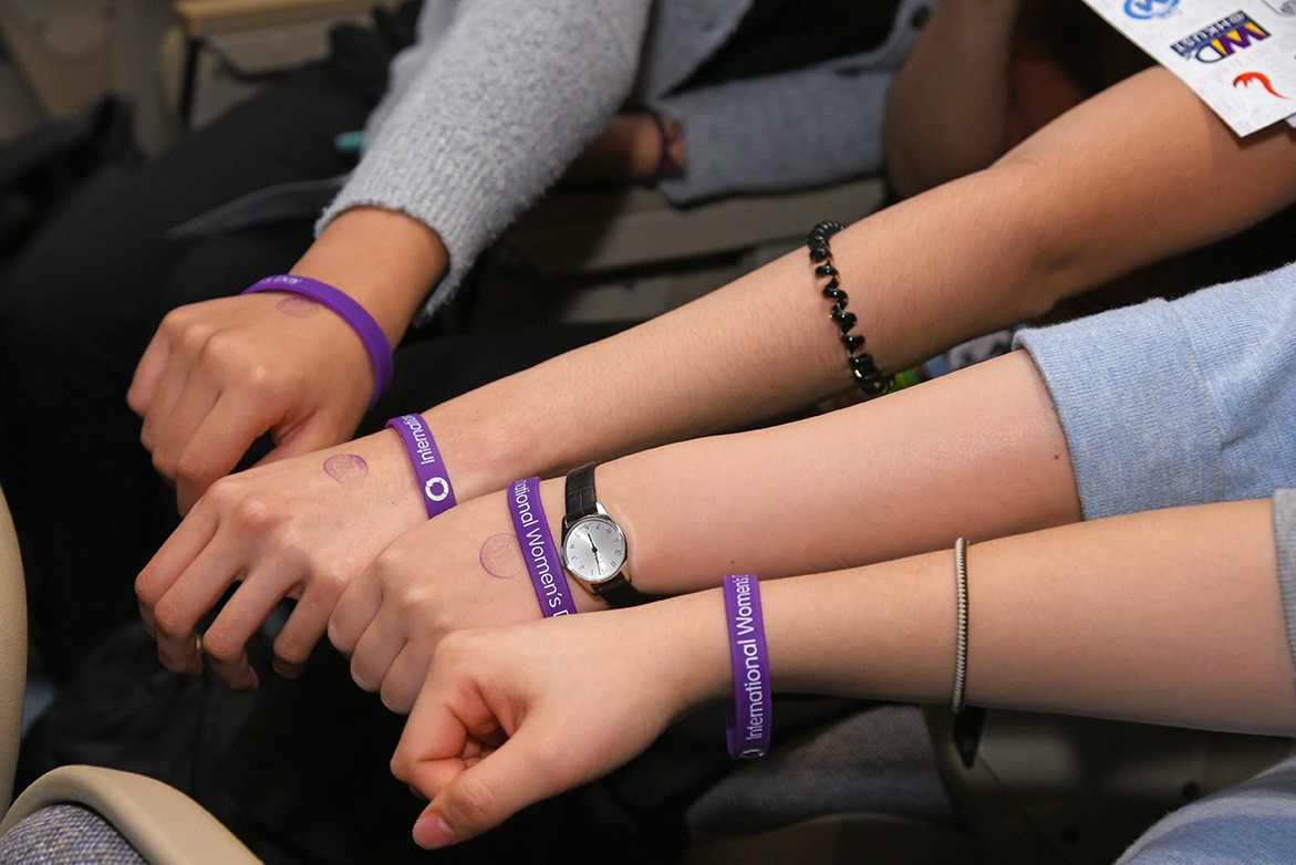 Four audiences putting their hands together showing the IWD wristband.
