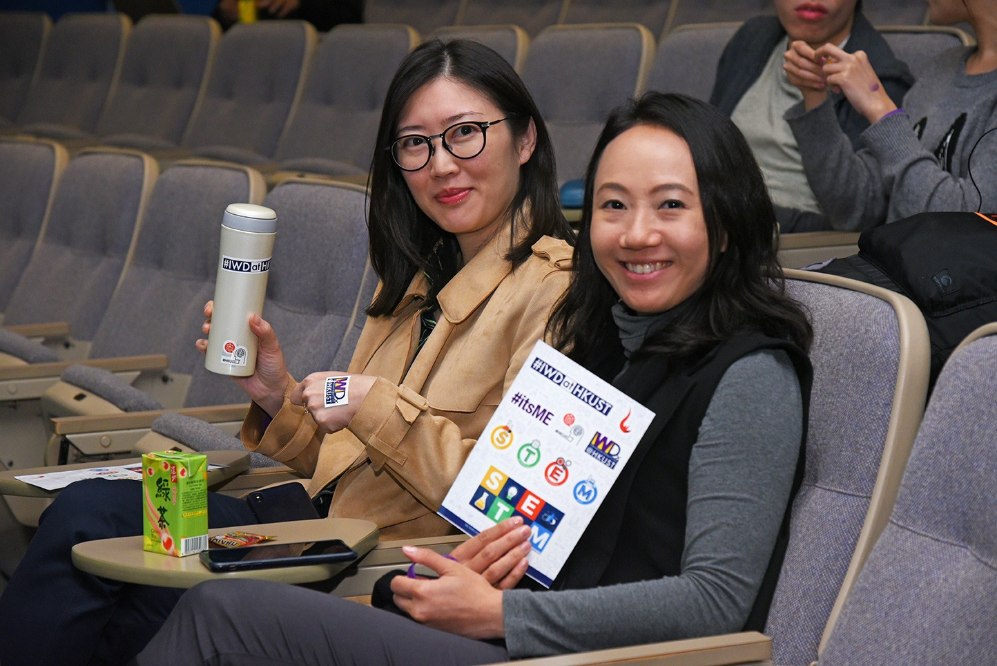 Two audiences holding IWD stickers and a bottle with stickers.