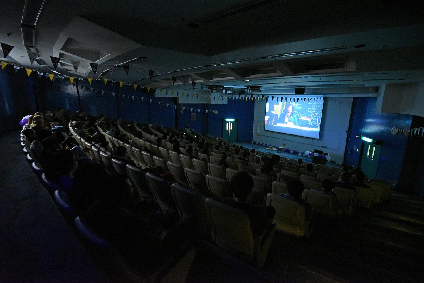 Audiences enjoying the movie in dim lighting.