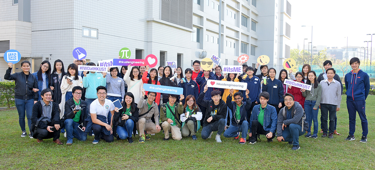 A group photo of 41 participants holding photo props on grass.