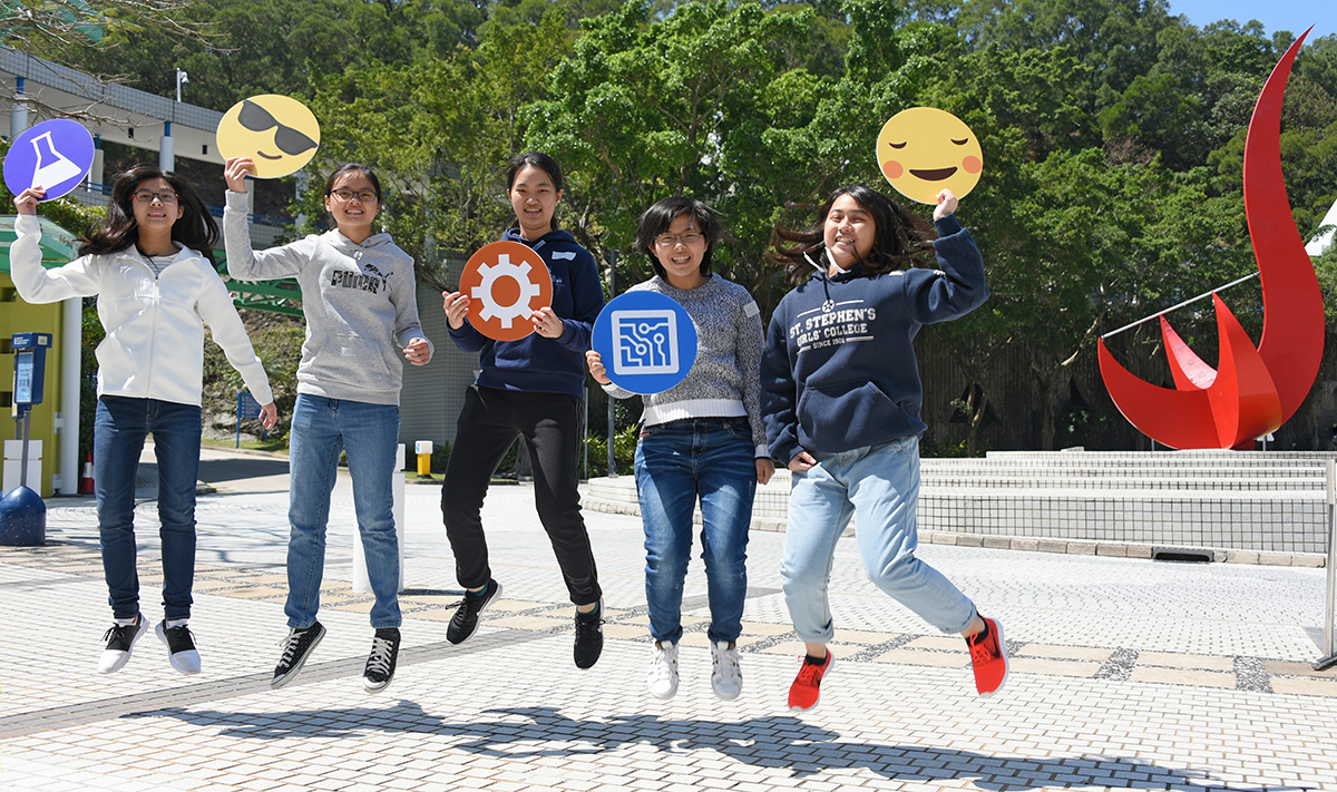 5 Students holding photo props and jumping in front of HKUST's Red Bird Sundial.