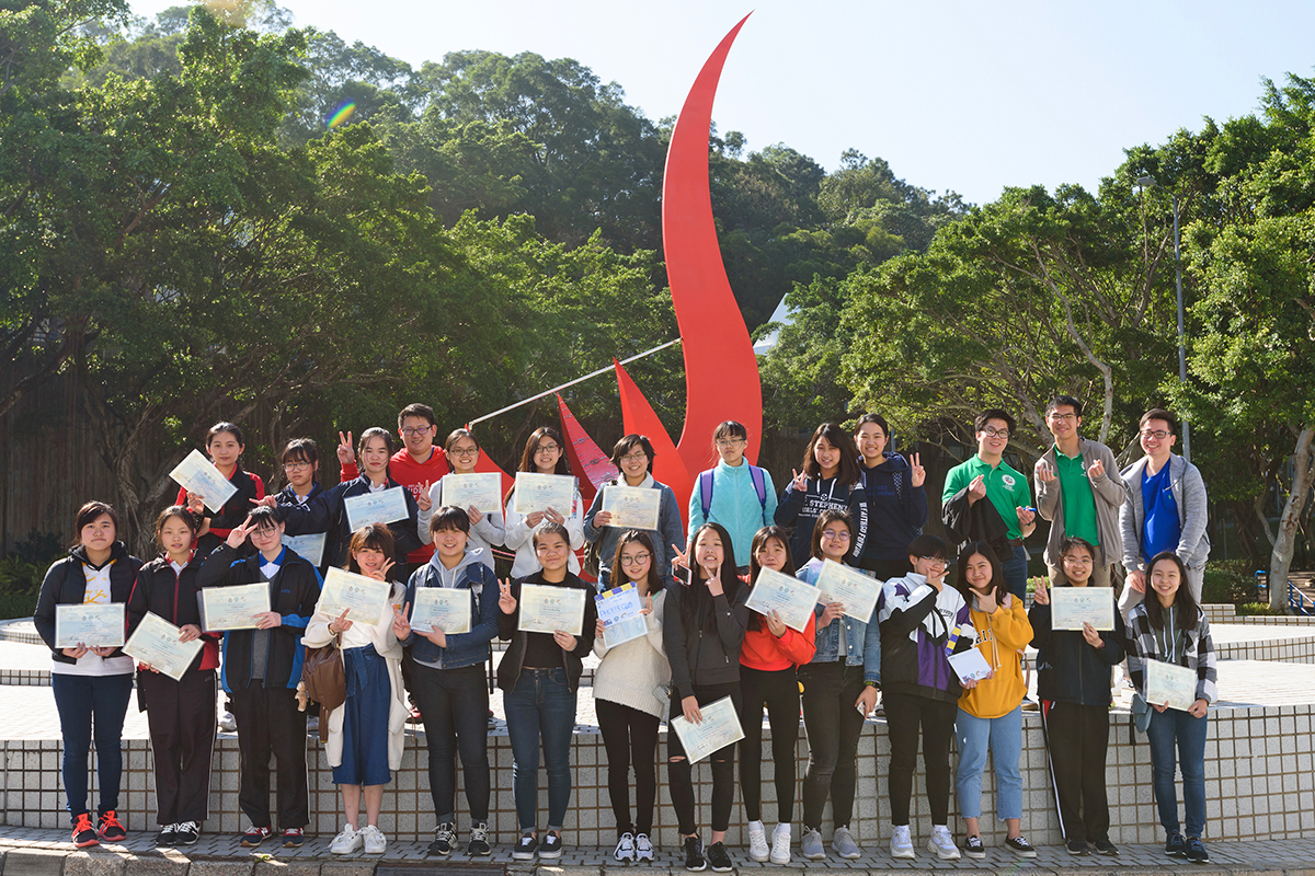 A group photo of 27 students holding their certificates.